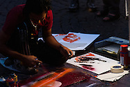 A street painting artist uses  a acrylic spray technique to render artistic impressions of Rome