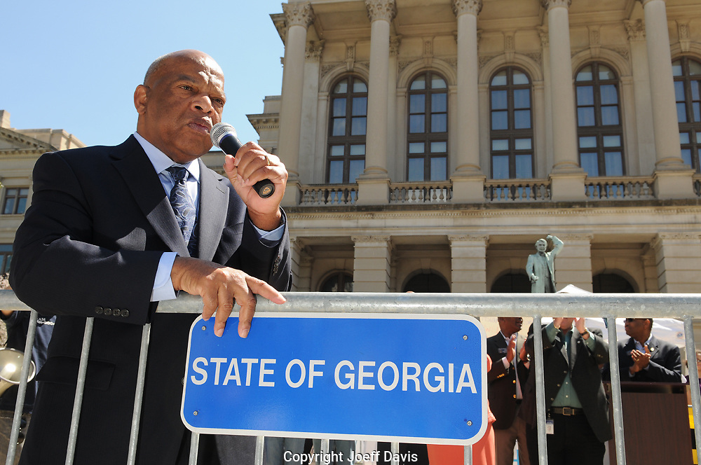 ATLANTA, GA - MARCH 24 , 2011: &quot;You must not give up,&quot; Representative John Lewis told the thousands of protesters gathered outside the Georgia capitol to loudly oppose two controversial pieces of legislation aimed at cracking down on illegal immigration. &quot;We are all brothers and sisters we are all one family, &quot; Lewis shouted to the cheering crowd. &quot;If anyone of us is illegal we are all illegal. There are no illegal human beings. If any of you get arrested and go to jail I am prepared to go to jail with you. We will get justice in the state of Georgia!&quot;<br /> <br /> Police estimated approximately 6,500 people attended the event. Chanting and holding signs with such messages as &quot;No human is illegal&quot; and &quot;Stop racial profiling,&quot; the crowd urged Gov. Nathan Deal to veto whichever bill state lawmakers ultimately approve. <br /> <br /> Between speeches by immigration advocates, Democratic state lawmakers and religious leaders, the Indigo Girls performed for the large crowd. <br /> <br /> Both the House and Senate have passed their own legislative packages aimed at undocumented immigration. The bills would provide stiff penalties for people who transport or offer aid to undocumented immigrants and give police the authority to check a suspect's immigration status if the officers have &quot;probable cause,&quot; among other changes.<br /> <br /> Critics, including civil and human rights groups, say the legislation would severely hinder Georgia industries dependent on migrant labor and likely trigger tourism and product boycotts.