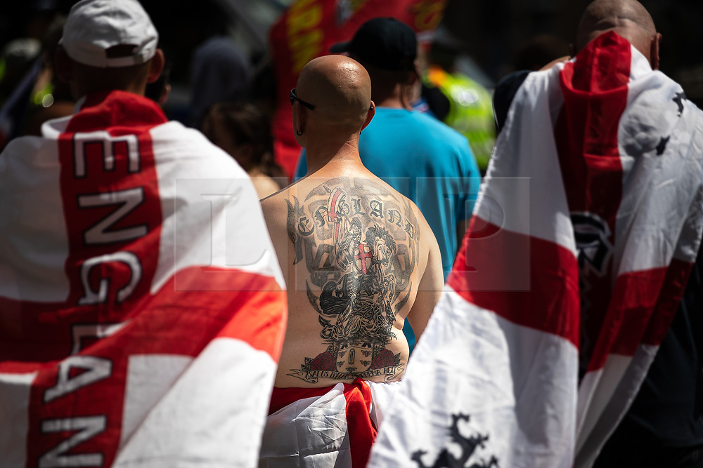 "© Licensed to London News Pictures . 07/07/2018 . Leeds , UK . A man with a horse riding crusader England tattoo on his back at an anti-Islam demonstration by supporters of jailed EDL founder Tommy Robinson , including those from the "" Yorkshire Patriots "" and "" First for Britain "" , in Leeds City Centre , opposed by anti-fascists . Robinson ( real name Stephen Yaxley-Lennon ) was convicted of Contempt of Court in May 2018 after committing a second offence , whilst serving a suspended sentence for the same crime . Photo credit : Joel Goodman/LNP"