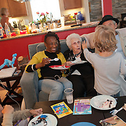 little boy holding up four fingers to show his age to grandma and great-grandma