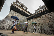 Tourists using umbrellas as they explore Matsuyama Castle, Matsuyama, Eihime, Japan.. Saturday, June 27th 2015