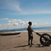 Beach Motadikin, on the East Timor border, a young boy waiting the boat to carry the fish.