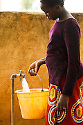 A girl fills a bucket of water from a tap outside the Fatao primary school in the village of Fatao, Mali on Tuesday August 31, 2010.