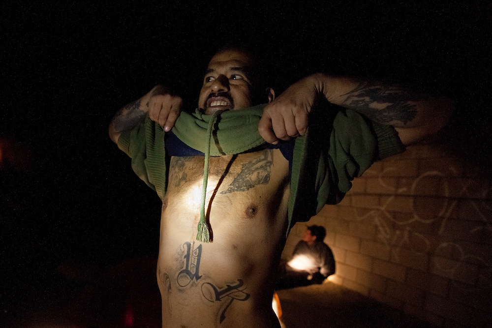 A man who is under the influence of methamphetamine shows his tattoos to officers. The man sitting on the ground behind him was arrested for possession of methamphetamines with intent to distribute. Dec. 8, 2011. Oxnard, Calif. (Photo by Gabriel Romero ©2011)
