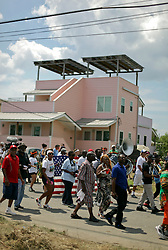 29 August 2015. Lower 9th Ward, New Orleans, Louisiana.<br /> A second line passes down Tennessee Street in front of Brad Pitt inspired make it Right homes. <br /> Photo credit©; Charlie Varley/varleypix.com.