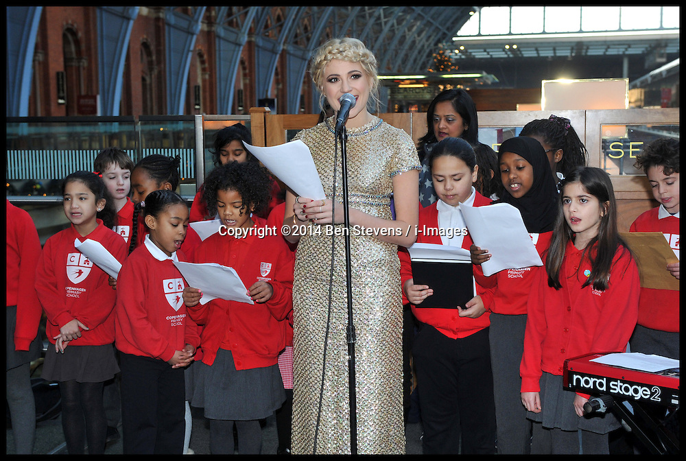Image &copy;Licensed to i-Images Picture Agency. 16/12/2014. London, United Kingdom. <br /> <br /> Pixie Lott busks at St Pancras Station, London,  in support for Penny for London charitable revolution.<br /> <br /> Pictured is Pixie Lott singing christmas carols with children from Copenhagen Primary School.<br /> <br /> Picture by Ben Stevens / i-Images