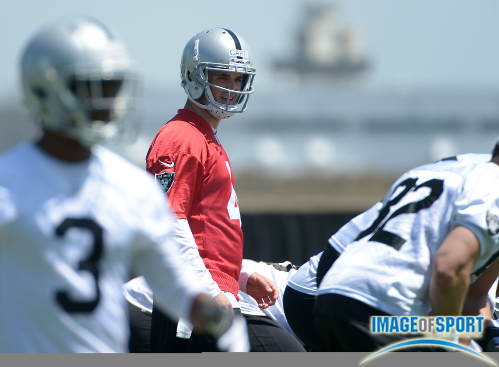 May 16, Alameda, CA, USA; Oakland Raiders quarterback Derek Carr (4) takes the snap at rookie minicamp at the Raiders practice facility.