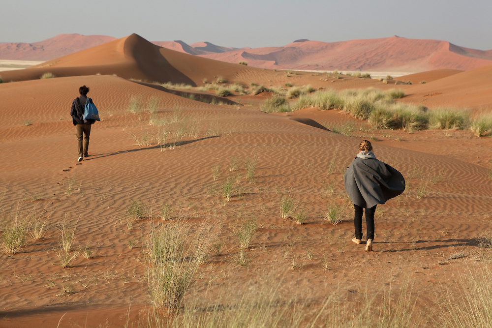 A couple of tourists take a walk at the dunes in Sossusvlei National Park, Namibia.
