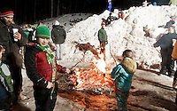Michael Morrone takes a break from sliding and enjoys roasting marshmallows over the fire during the Sledding Party behind Memorial Park in Laconia Friday evening.  (Karen Bobotas/for the Laconia Daily Sun)
