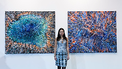 "© Licensed to London News Pictures. 19/05/2016. London, UK. Artist, Victoria Kovalenchikova, is seen with two of her works (L to R) ""The Earth"" and ""The World"".  Art16 opens at Olympia, in west London.  Now in its fourth edition, the fair brings together over 100 galleries from more than 30 countries showcasing a diverse cross-section of work by contemporary artists from around the world for buyers and art enthusiasts to visit. Photo credit : Stephen Chung/LNP"