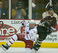 10/10/06 University of Nebraska at Omaha's Dan Charleston slips on the ice as  Mantitoba's Rob Smith watches during an exhibition game..(Chris Machian/Prairie Pixel Group)..