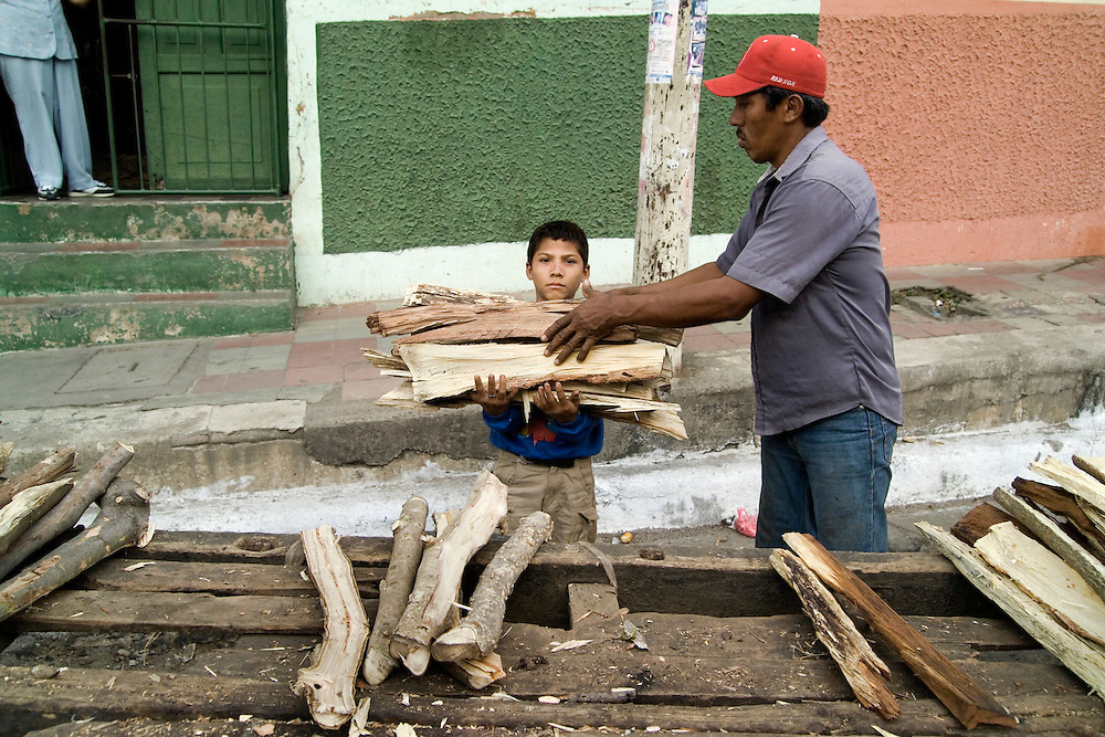 A boy helps his father unload wood from a cart in León, Nicaragua.