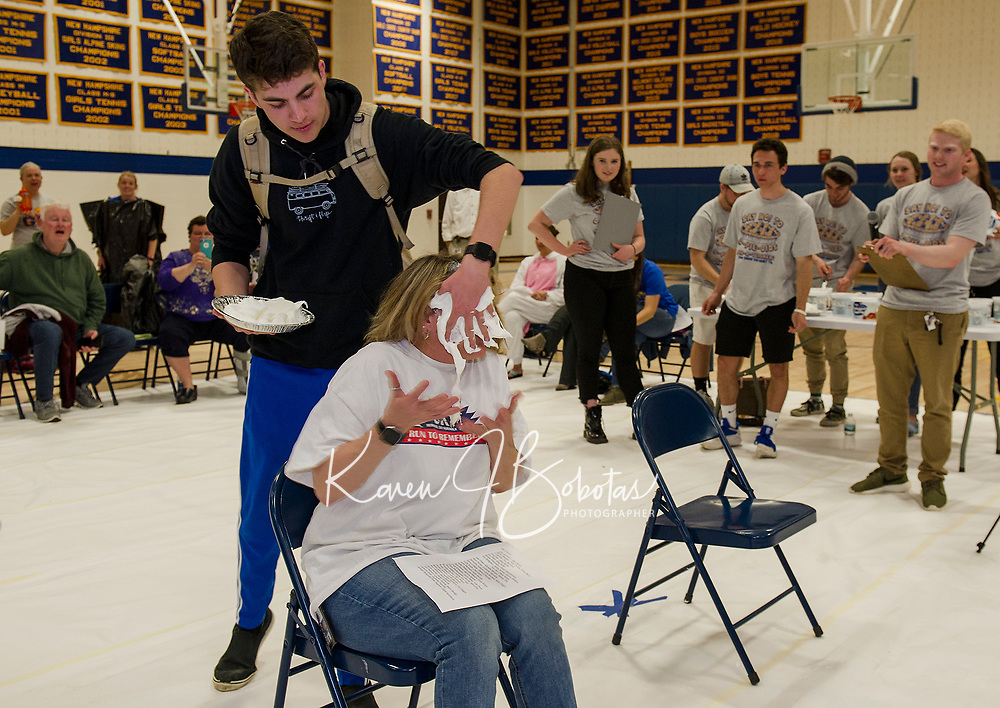 """Sam Sawyer comes from behind to """"pie"""" his mom Monica Sawyer during Gilford High School's """"Pie a Teacher"""" fundraiser to benefit The Doorway at LRGH on Friday afternoon. (Karen Bobotas/for the Laconia Daily Sun)"""