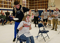 "Sam Sawyer comes from behind to ""pie"" his mom Monica Sawyer during Gilford High School's ""Pie a Teacher"" fundraiser to benefit The Doorway at LRGH on Friday afternoon. (Karen Bobotas/for the Laconia Daily Sun)"