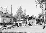 Street View of rural area with wooden houses with women washing clothes around a well 1920s-1930s, Finland