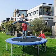 Nederland Amsterdam 29 maart 2011 20110329 Nieuwbouwwijk Ijburg, kinderen spelen, zij springen op een trampoline, in de achtertuin van een van de grote woningen met individuele architectuur die aan het water grenzen. Individueel vormgegeven architectuur. Noot: Fotograaf heeft toestemming gekregen van volwassene op de achtergrond om de beelden te maken. , samenleven, sociaal gedrag, sociale, sociale banden, sociale cohesie, sociale samenhang, socialisering, socialising, spare time, speel plek lokatie, speellokatie, speelplaats, speelplek, speelplekken, speelruimte, speels, speelse, spelen, spelende, spelenderwijs, sportief, sportieve, sportive, springen, sprong, stadsdeel, stadsuitbreiding, stadswijk, sunny, sunshine, tezamen, together, vastgoed, ventje, ventjes, vernieuwing, vinex, vinex-locaties, vinex-wijken, vinexbuurt, vinexlocatie, vinexlokatie, vinexwijk, voorgevel, voorjaar, vrienden, vriendje, vriendjes, vriendschap, vriendschappelijk, vrij, vrije tijd, warm weer, wijk, wijken, wonen, woning, woningbehoefte, woningen, woningmarkt, woningvoorraad, woonbuurt, woonbuurten, woonlast, woonlasten, woonwijk, woonwijken, woz waarde, Youth, zichzelf vermaken, zonlicht, zonnetje, zonnig, zonnig weer, zonnige dag, zweven Foto: David Rozing