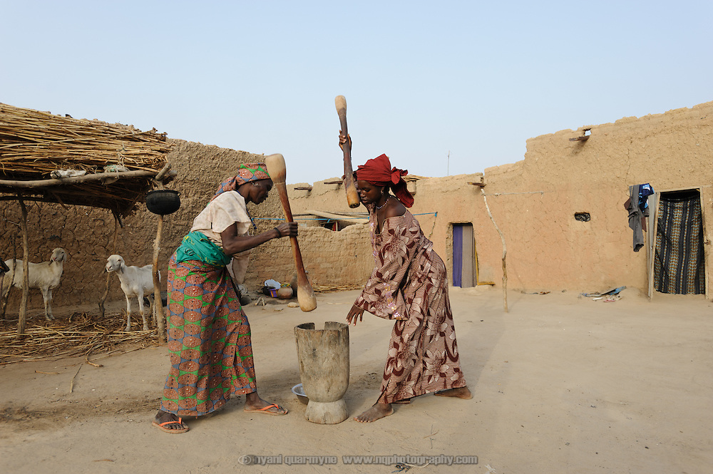 Halima Moussa and her aunt, Fati Abdou, pounding millet for the evening meal at the home of Halima's father-in-law, Alhaji Maman Bilali, in Tessaoua in Niger. Following a failed harvest, Halima and her children have moved in with Bilali and his family, as her husband has migrated to Maradi in search of work.