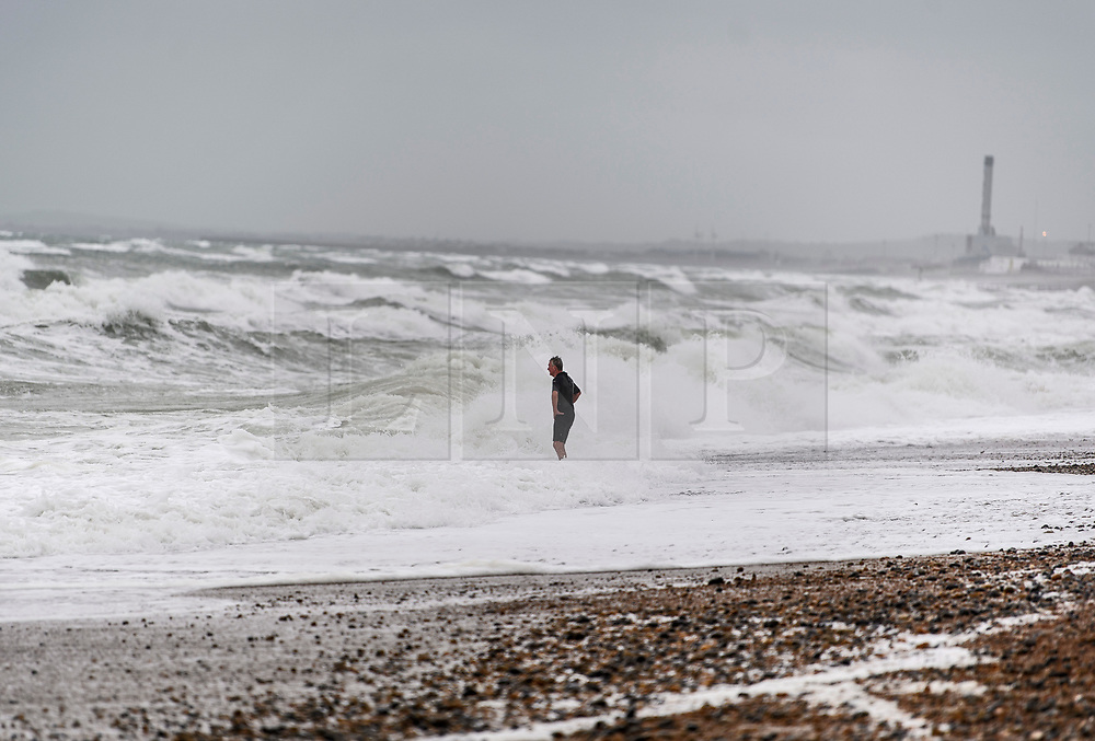 © Licensed to London News Pictures. 18/09/2018. Brighton, UK. A man braves a dip in rough sea waters during wet and windy conditions on the sea front at Brighton. The recent warm spell is set to change for many over the next few days in the south. Photo credit: Ben Cawthra/LNP