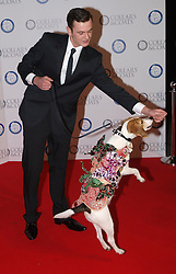Shaun Matthews gets Bibi the 1 year Beagle wearing a coat , collar and lead designed by Vivienne Westwood at  the Collars & Coats Gala ball, the Battersea Dogs Home, November 8, 2012. Photo by i-Images.