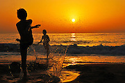 Silhouette of two children playing on the Beach at sunset