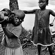 Two young Afro Colombian children collect firewood on the banks of the Rio Atrato in Choco, Colombia. They are some of the countries more than 2 million internally displaced. The jungle area around their village is being fought over by both leftwing rebel groups and rightwing paramilitaries. The inhabitants of many villages have fled to Bellavista. This town was the site of a massacre in May 2002 when a homemade mortar fired by FARC rebels exploded on the roof of a church and killed 119 civillians hiding inside.<br />