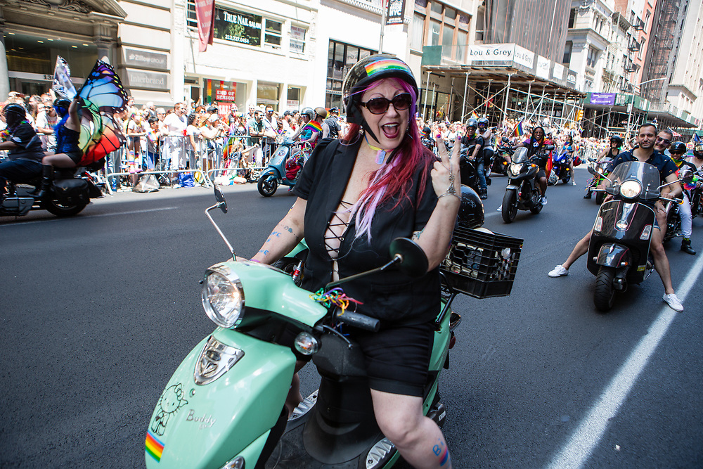 New York, NY - 30 June 2019. The New York City Heritage of Pride March filled Fifth Avenue for hours with participants from the LGBTQ community and it's supporters. Motorcycles led the march, and this woman rode a Buddy 50 motor scooter in the midst of much larger machines.