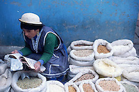 June 1995, Cuenca, Ecuador --- A women reads a newspaper while selling grains at a market in Cuenca, Ecuador. --- Image by © Owen Franken/CORBIS