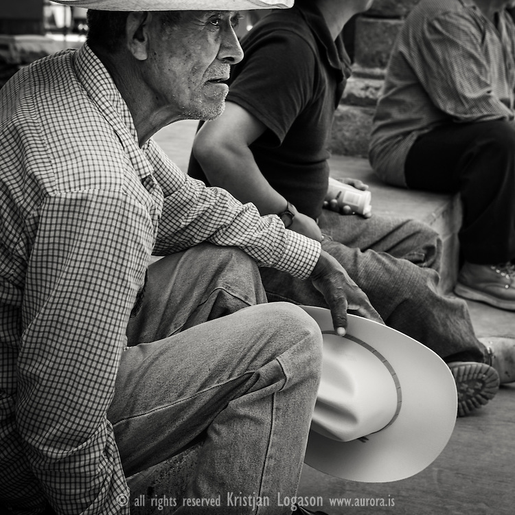Man with hat in his hand resting from a buissy day at the market in Tlacolulu