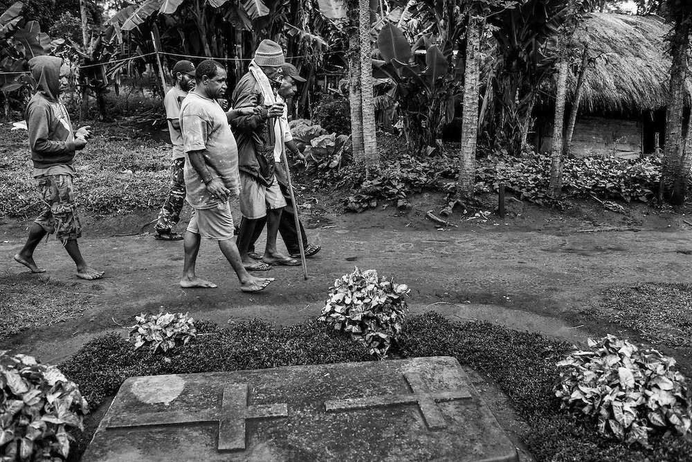 Public Health Development Foundation (YPKM), a local NGO in Wamena, helps bring David who is in the late stages of AIDS to the Emergency Room for immediate medical assistance. Along the way, he walked past a grave of a baby who died a month earlier from a sudden illness after contracting the HIV virus from the mother.<br /> <br /> David has been HIV-positive for almost 4 years.  His wife is also HIV-positive and they are both taking ARV medication.  However, David did not take his medication properly and his health has declined significantly.  Living in a rural area of Lani Jaya, David's village lacks an adequate health facility, and he must travel hundreds of miles to Wamena to receive care.  Staying in a relative's honai or traditional hut, David's condition deteriorated.  YPKM or the Foundation for the Development of Public Health in Wamena chartered a vehicle to take David to the emergency room.  Frail and in poor health, David barely made it to the hospital.  His white blood cell count was dismal at 24, instead of the typical 700.  At the hospital, David received saline solution and medicines that significantly improved his condition.  YPKM also gave David rice and milk to help him with his recovery.  Nevertheless, after three days in the hospital, David forcefully checked himself out because he wanted to conduct the adat ritual, and the health staff could not prevent him from leaving.  David spent several hundred dollars to purchase two pigs for the ritual.  However, his health deteriorated to the point where he was unable to stand up on his own.  A week after checking himself out from the hospital, David chartered a vehicle to go back to his village to die.