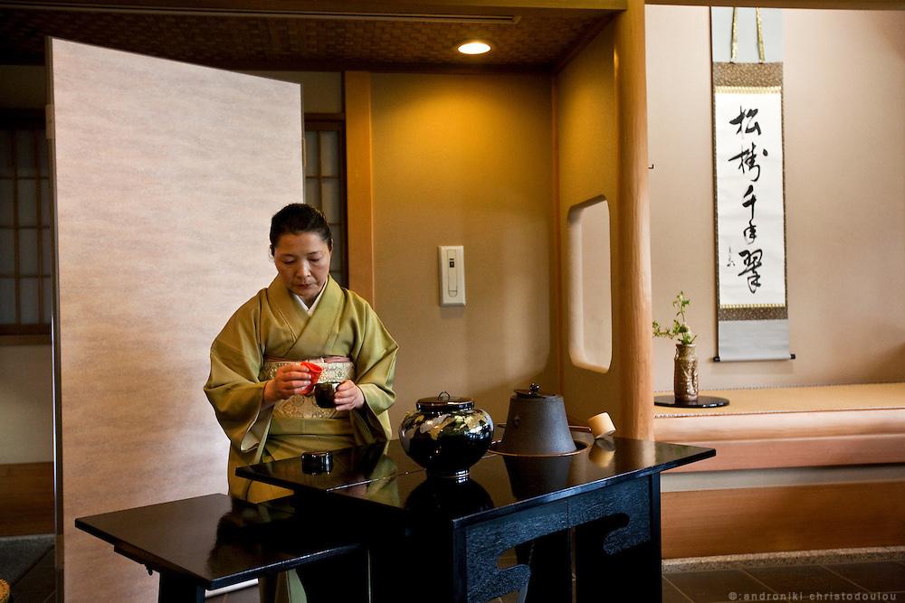 Japanese woman preparing tea during a tea ceremony.