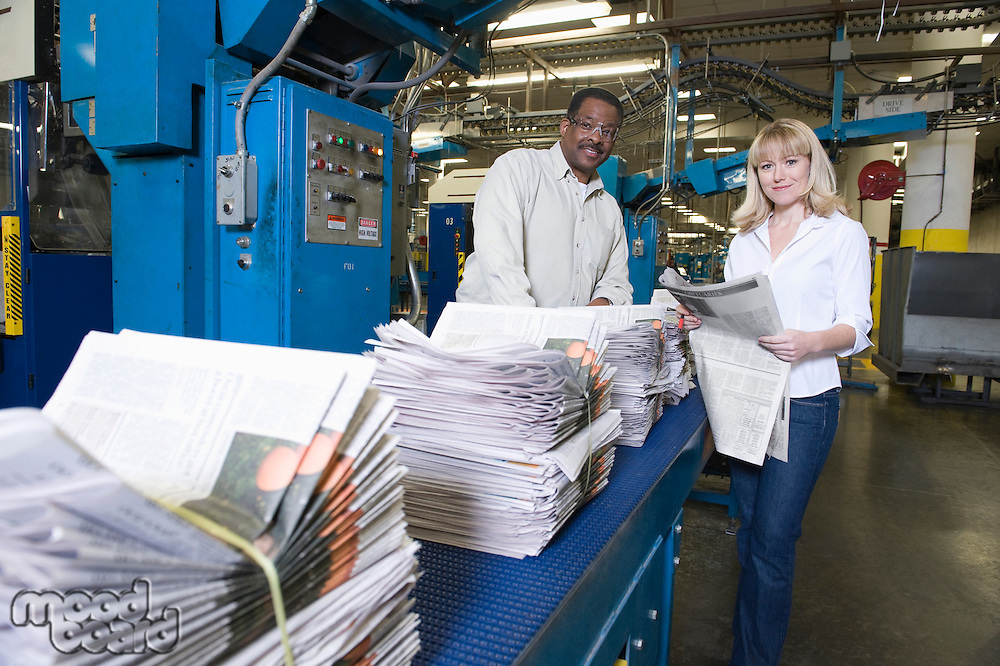 Man and woman working in newspaper factory