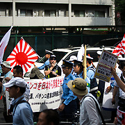 "TOKYO, JAPAN - JULY 16: Japanese nationalists holding Japanese maritime flags, escorted by police, took to the streets in a ""hate demonstration"" in Akihabara, Tokyo, Japan on July 16, 2017. The nationalists faced off with anti-racist groups who mounted counter protests demanding an end to hate speech and racism in Japan. (Photo by Richard Atrero de Guzman/AFLO)"
