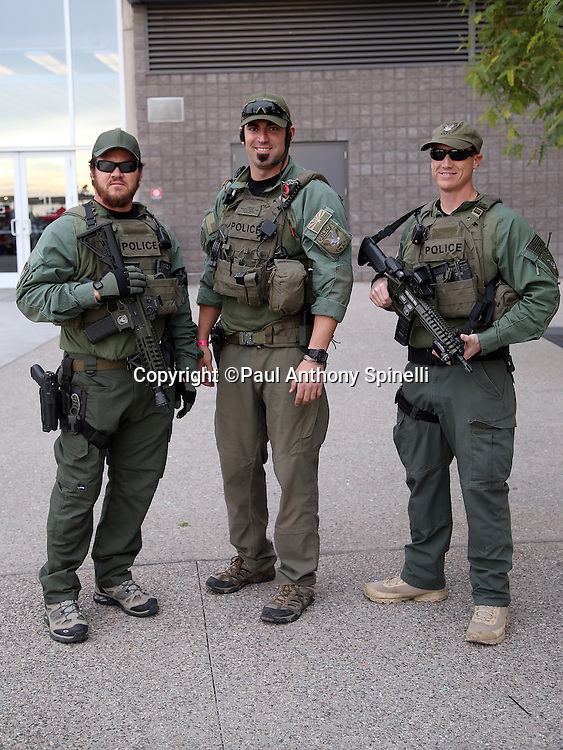 A trio of SWAT team members stands ready outside the stadium before the Arizona Cardinals NFL NFC Divisional round playoff football game against the Green Bay Packers on Saturday, Jan. 16, 2016 in Glendale, Ariz. The Cardinals won the game in overtime 26-20. (©Paul Anthony Spinelli)