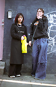 Two teenage girls standing against a wall smoking, Camden town, UK 2001