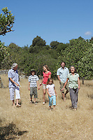 Three-generation family with two children (6-11) walking in field