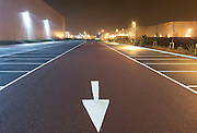 Pointing towards the viewer and the bottom of the picture near empty parking bay markings, a stencilled arrow directs traffic flow at the DIRFT warehouse logistics park in Daventry, Northamptonshire England. Bright light glows from the warehouse walls shining on to the car park creating an almost daylight landscape. This 365 acre site off Junction 18 of the M1 motorway is a hub for road, rail and service infrastructure, some 2.3m sq.ft. of distribution and manufacturing floorspace had been constructed by 2004 and occupiers including Tesco?s, Tibbett & Britten plc, Ingram Micro, Royal Mail, the W.H. Malcolm Group, Eddie Stobart Ltd, Wincanton and Exel, have been attracted to this logistics location.
