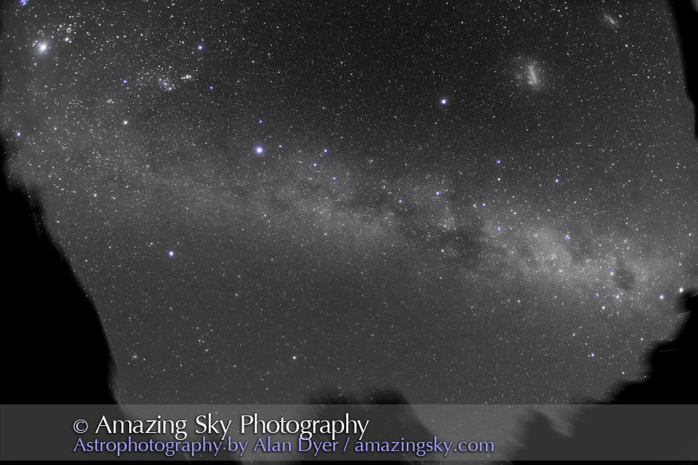 An ultrawide angle image of the southern Milky Way, taken from Coonabarabran, NSW, Australia, December 13/14, 2012, using an 15mm Canon full-frame fish-eye lens and Canon 5D MkII camera for a stack of 4 x 6 minute exposures at f/4 and ISO 800. Jupiter is at top left, Orion to the right of Jupiter. Sirius is left of centre, the large Gum Nebula is at centre, while the Carina Nebula, Crux and the Pointer stars, Alpha and Beta Centauri, are rising at lower right. The Magellanic Clouds are at upper right. Some high altitude haze added glows around bright stars. This version of the image has been processed to make the view better resemble what you see with the unaided eye, in a largely monochrome and softer view than the colourful and high-contrast views commonly presented in astrophotos. Even at that there is more fine structure present in the Milky Way than the unaided eye usually sees, though binoculars beging to reveal that smaller detail. I have left some colours in some stars and in the foreground of landscape scenes.
