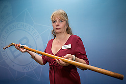 "© Licensed to London News Pictures . 07/08/2014 . Manchester , UK . Detective Chief Inspector Debbie Dooley of GMP's "" Xcalibre Task Force "" that tackles gun-related crime , holding a shotgun that fires live ammunition , disguised as a walking stick . Greater Manchester Police displays some of the cache of firearms and ammunition they collected during a two week firearms amnesty in July , at the force's North Manchester headquarters , this morning (7th August 2014) . GMP reports collecting 225 firearms and over 3000 rounds of ammunition during the fortnight amnesty of which , they say, over 80 of the weapons were illegally owned . Amongst the haul were rifles, shotguns , handguns and air weapons as well as imitation and antique firearms . Photo credit : Joel Goodman/LNP"