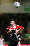 Matty Blair of Doncaster Rovers and Barnsley forward Mamadou Thiam (26) contest an aerial ball during the EFL Sky Bet League 1 match between Doncaster Rovers and Barnsley at the Keepmoat Stadium, Doncaster, England on 15 March 2019.