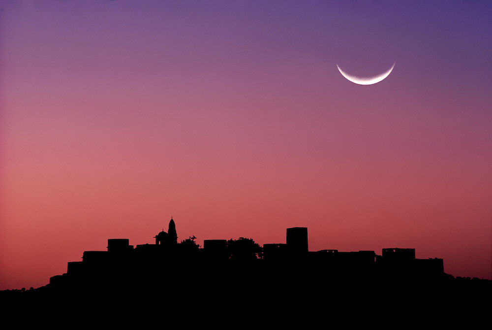 A crescent moon hangs above the silhouette of Jaipur in Rajasthan, India.