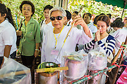 11 JULY 2014 - BANGKOK, THAILAND: A woman pours molten wax into a candle mold at Wat Pathum Wanaram for Asalha Puja Day. Making candles is a traditional way of making merit before the Rains Retreat because candles were essential in former times for both ceremonies and studying scriptures during night time. The large candles that are made and given to the temple to create illumination in the belief that such a gift will likewise illuminate the mind.  Asalha Puja is the day the Lord Buddha preached his first sermon to followers after attaining enlightenment. The day is usually celebrated by merit making and listening to a monks' sermons. It is also day before the start of the Rains Retreat, the three month period when monks stay in their temple for intense mediation and spiritual renewal.    PHOTO BY JACK KURTZ