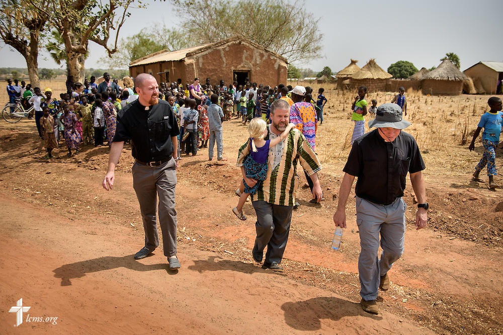 LCMS Missionaries, the Rev. Ryan McDermott, the Rev. Micah Wildauer, and the Rev. Gary Schulte, depart a youth music presentation in the former church building next to the Lutheran Church of Togo in Mire on Sunday, Feb. 12, 2017, in Mire, Togo. Wildauer is carrying his daughter Eliza. LCMS Communications/Erik M. Lunsford