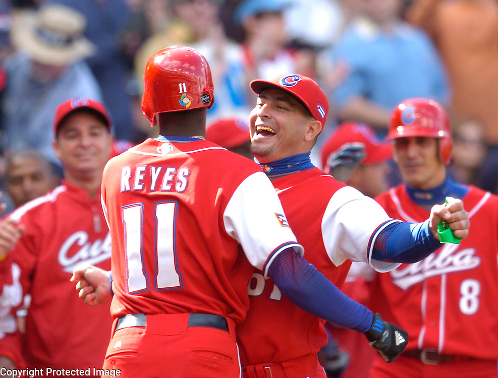 Team Cuba's Rudy Reyes #11 is congratulated after scoring the 2nd run in the 7th inning against Team Dominican Republic  in Semi-Final action of the World Baseball Classic at PETCO Park, San Diego, CA.