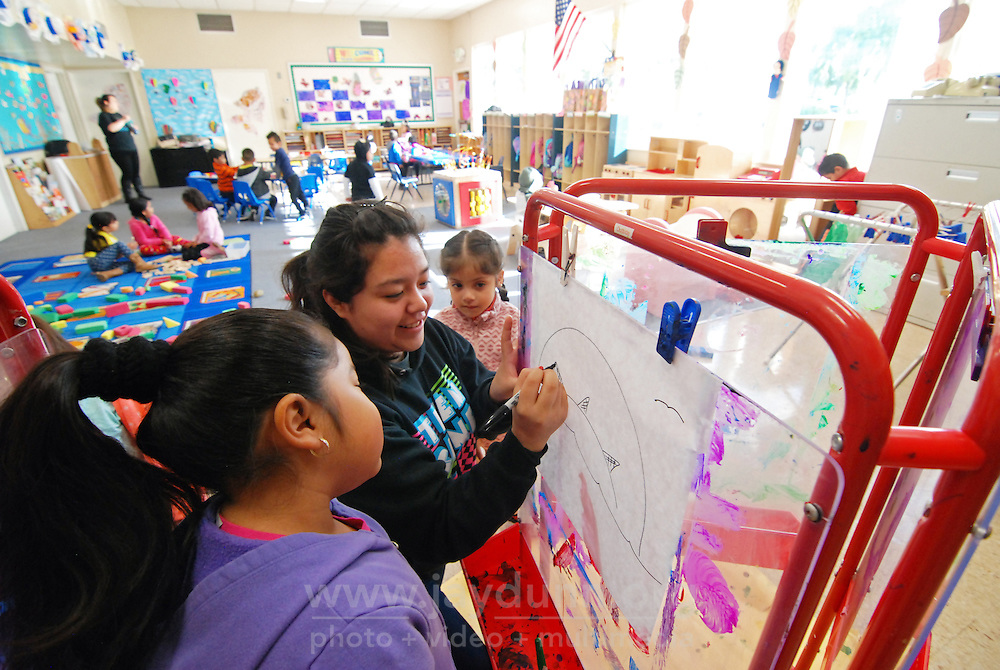 At the Hebbron Family Center in Salinas, assistant Matilde Peña draws a tropical island on which chilldren in the Tiny Tots program will paint.