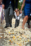 A toddler walks across a bed of flowers during a wedding at Plumb Jack, Squaw Valley, Tahoe, California.