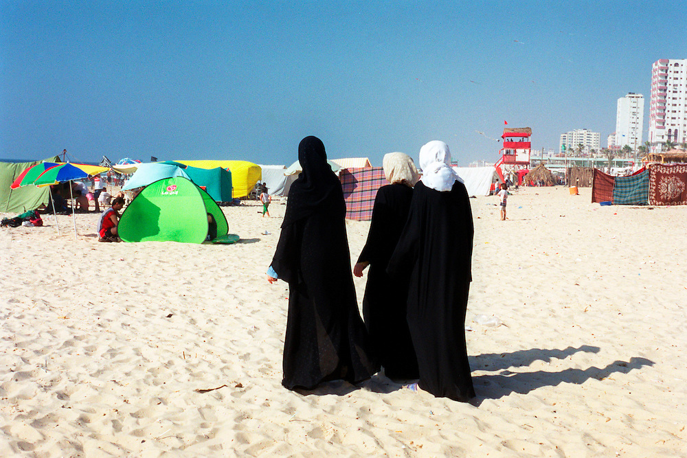 Women fully clothed in traditional Islamic wear for women stroll down the beach on the Muslim day of rest in the Mediterranean coastal city of Gaza Friday July 27, 2001. Despite the 11 months of violence Israelis and Palestinians take a break to enjoy the mediterrenean beaches and the Dead Sea, where under growing tensions and in the case of Gaza under closure people try to  make the best of their summer and carry on a normal life. (AP PHOTO/Elizabeth Dalziel)