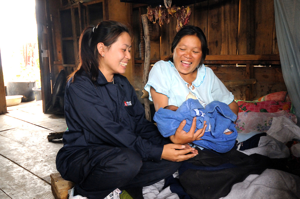 "Sia Thorthongyer, age 20, visits her supervisor, Mines Advisory Group (MAG) women's Team Leader, Peng Souvanthon, age 26, with her 2 day old son and 6 year old daughter at home.  Even at 8 months pregnant she worked in remote Nong Het field locations clearing bombs up until the day she gave birth. ..She says, ""I'm happy to have helped my village and made it more safe for farming.""  And when asked about competing with the MAG men's demining teams she says ""Yes, if the men clear 2,000 sq m of land per day, then we women want to do even more.""..Laos was part of a ""Secret War"", waged within its borders primarily by the USA and North Vietnam.  Many left over weapons supplied by China and Russia continue to kill.  However, between 90 and 270,000 million fist size cluster bombs were dropped on Laos by the USA, with a failure rate up to 30%.  Millions of live cluster bombs still contaminate large areas of Laos causing death and injury.  The US Military dropped approximately 2 million tons of bombs on Laos making it, per capita, the most heavily bombed country in the world.  ..The women of Mines Advisory Group (MAG) work everyday under dangerous conditions removing unexploded ordinance (UXO) from fields and villages. ..***All photographs of MAG's work must include (either on the photo or right next to it) the credit as follows:  Mine clearance by MAG (Reg. charity)***."