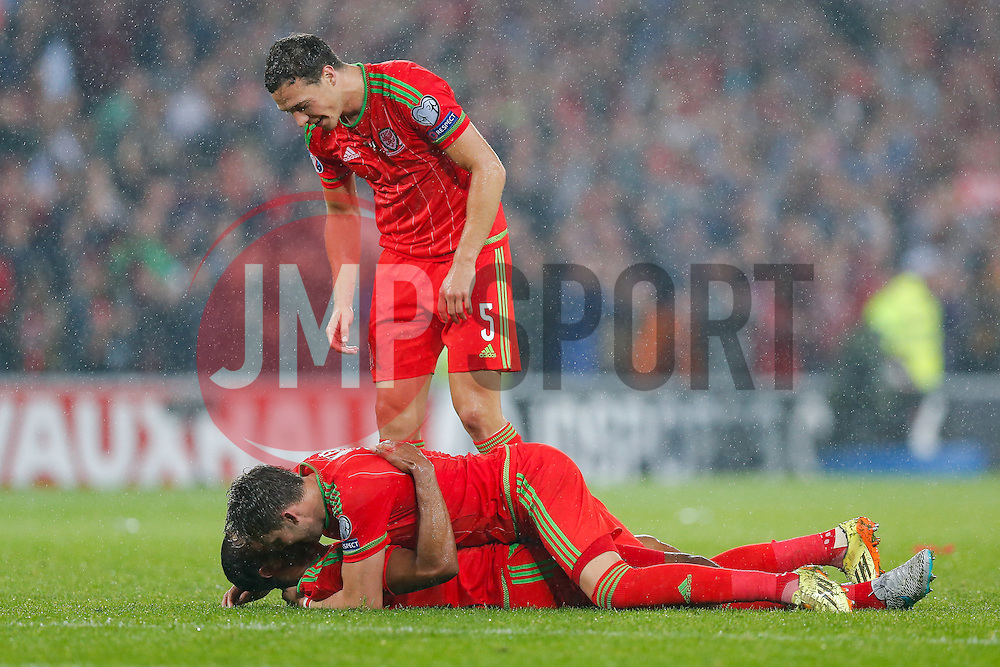 Chris Gunter (Reading) hugs Ashley Williams (Capt) (Swansea City) on the floor as James Chester (Hull City) looks on after Wales win the match 1-0 to top their UEFA2016 Qualifying Group - Photo mandatory by-line: Rogan Thomson/JMP - 07966 386802 - 12/06/2015 - SPORT - FOOTBALL - Cardiff, Wales - Cardiff City Stadium - Wales v Belgium - EURO 2016 Qualifier.