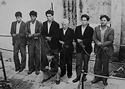 Members of the Banda Giuliano Salvatore, arrested and chained, undated black and white photograph from the exhibition No Mafia Memorial, in Palermo, Sicily, Italy. Salvatore Giuliano was a bandit wanted by the police, who was also involved in the Movement for the Independence of Sicily. The No Mafia Memorial explores the growth and history of the mafia, and its impact on the Sicilian population. Picture by Manuel Cohen