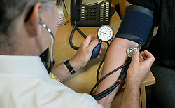 File photo dated 10/09/14 of a GP checking a patient's blood pressure. GP leaders are looking at ways doctors can earn extra cash from NHS patients by offering treatments not available on the health service.